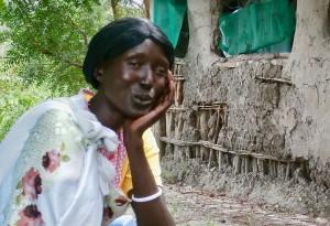 Woman repairs mudhut homes